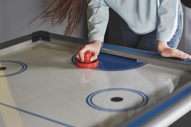 Mãos de jovens segurando o atacante na mesa de air hockey na sala de jogos