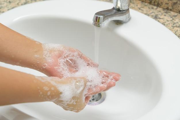 Mãos de lavagem da mulher do close up com sabão sob o torneira com água no banheiro.