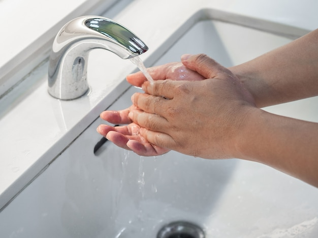 Mãos de lavagem do homem do close up sob o torneira com água no banheiro.