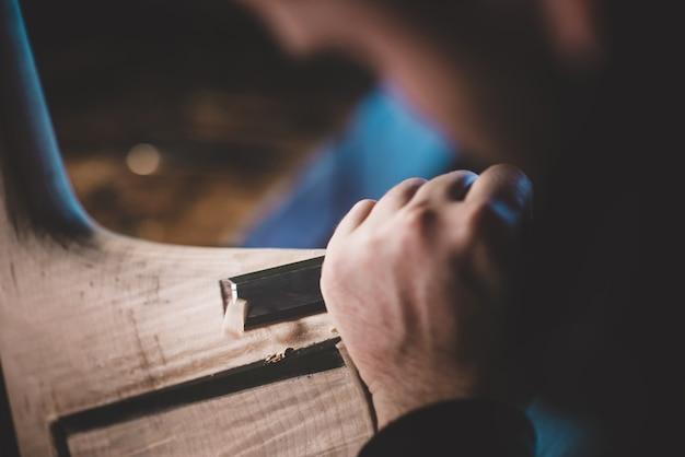 Mãos de luthier artesão lixar, construindo um contrabaixo