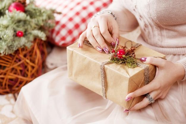 Mãos de lwoman segurando uma caixa de presente. natal, ano novo.