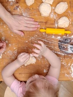 Mãos de mãe e filha amassam a massa em uma mesa de madeira