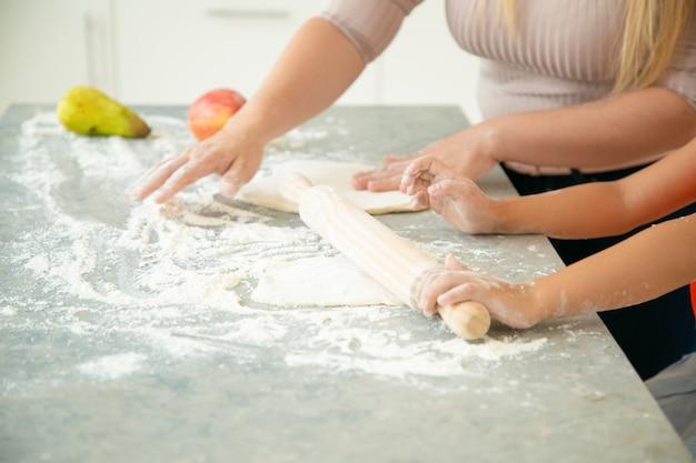 Mãos de mãe e filha rolando massa na mesa da cozinha. menina e a mãe dela fazendo pão ou bolo juntas. close, foto recortada. conceito de cozinha familiar