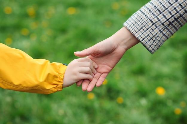 Mãos de mãe e filho alcançando uma à outra. suporte, ajuda e confiança.