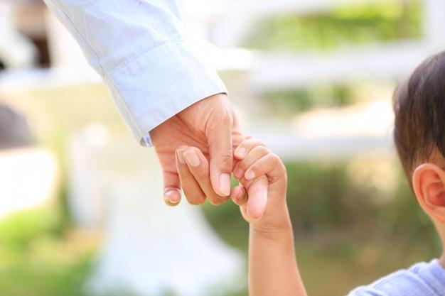 Mãos de mãe e filho. close-up menino segurando as mãos da mãe.