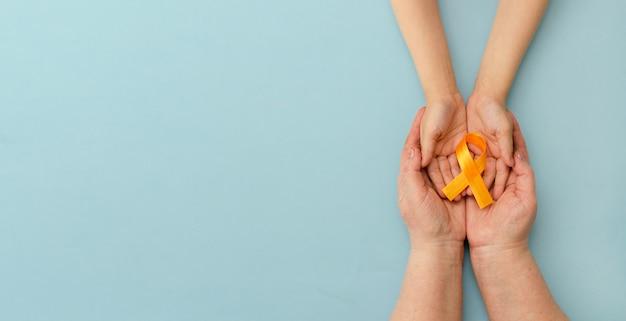 Mãos de mãe e filho seguram uma fita laranja sobre fundo azul. dia mundial da esclerose múltipla