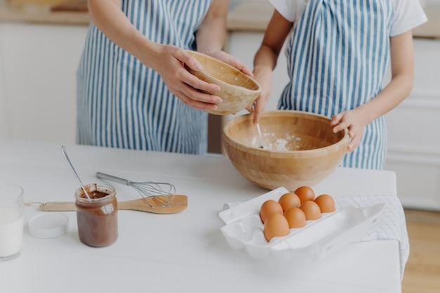 Mãos de mães e filhas misturando ingredientes para preparar massa e assar bolos saborosos