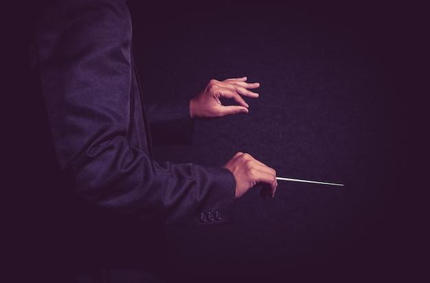 Mãos de maestro de orquestra, diretor de músico segurando a vara no fundo escuro