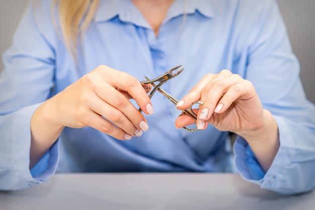 Mãos de manicure profissional segurando ferramentas de manicure vestindo roupas de trabalho azuis no salão de beleza