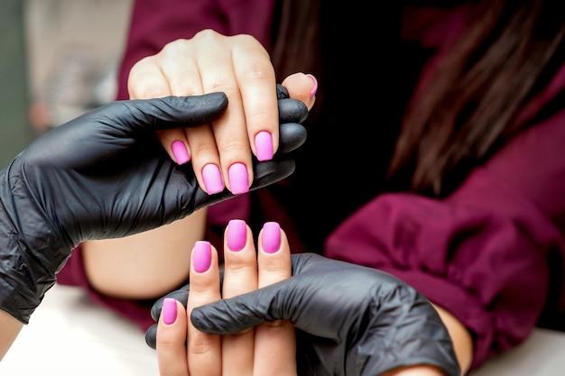 Mãos de manicure segurando unhas femininas com esmalte rosa em salão de beleza