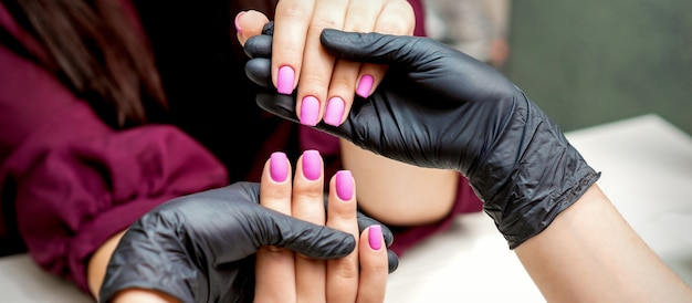 Mãos de manicure segurando unhas femininas com esmalte rosa