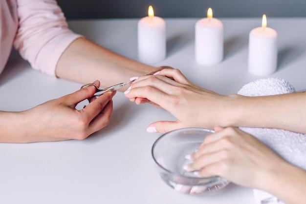 Mãos de manicure usa uma tesoura de unha cosmética de metal para cortar cutícula de unhas do cliente do sexo feminino. mão de mulher, recebendo procedimento de manicure com ferramenta de cuidados com as unhas.