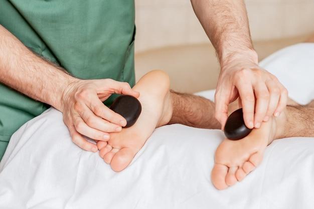 Mãos de massagista fazendo massagem nos pés da mulher por pedras quentes no spa.