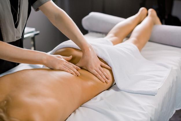 Mãos de massagista feminina massageando as costas do cliente mulher, deitado no sofá no centro de spa médico moderno