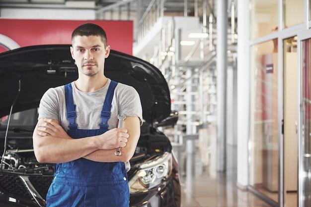 Mãos de mecânico de automóveis com uma chave inglesa na garagem.