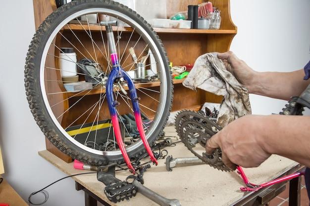 Mãos de mecânico de bicicleta limpando bicicleta com corrente