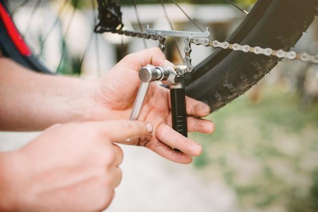 Mãos de mecânico de bicicletas ajustam a corrente da bicicleta com ferramentas de serviço.