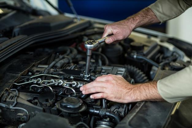 Mãos de mecânico de manutenção de um carro