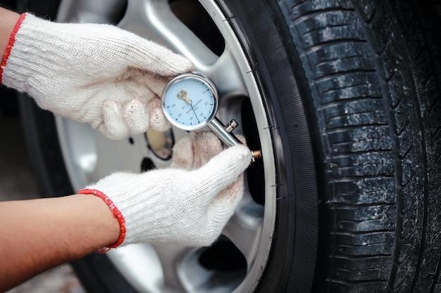 Mãos de mecânico verificar a pressão de ar do pneu