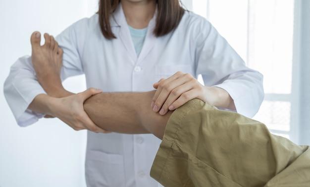 Mãos de médica fazendo fisioterapia, estendendo a perna e o joelho de um paciente do sexo masculino.