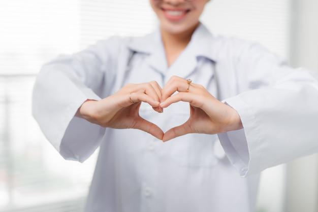 Mãos de médica fazendo formato de coração de perto