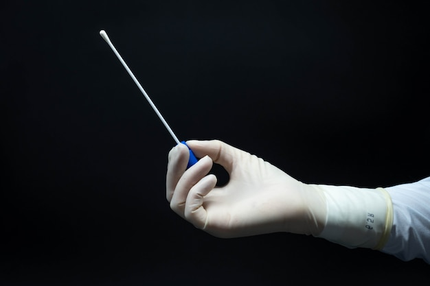 Mãos de médico com luvas estéreis segurando uma amostra de teste pcr para covid-19 de perfil, fundo preto