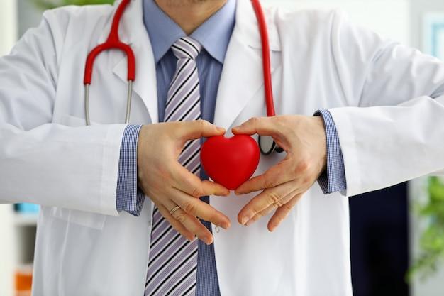 Mãos de médico de medicina masculina segurando e cobrindo coração de brinquedo vermelho