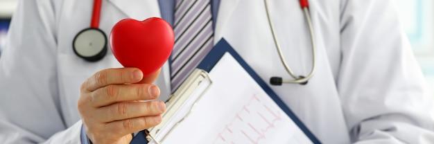 Mãos de médico de medicina masculina segurando um coração vermelho de brinquedo