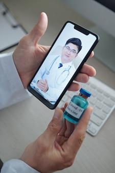 Mãos de médico segurando frasco de vacina contra coronavírus durante uma videochamada para seu colega de outro hospital