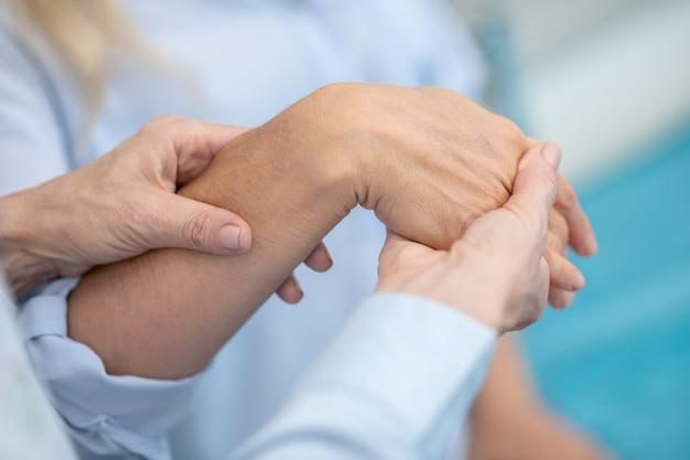 Mãos de médicos experientes dobrando a mão do paciente durante o exame, os rostos não são visíveis