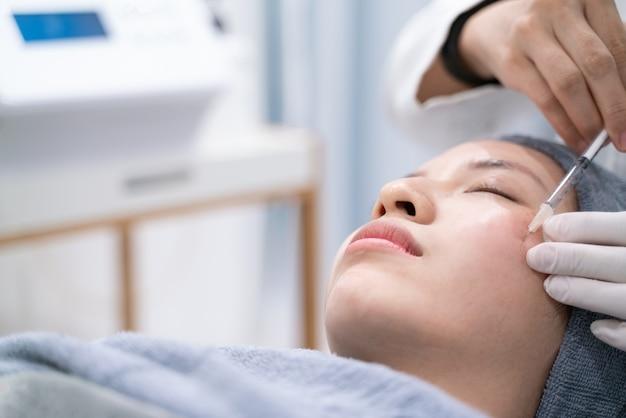 Mãos de médicos fazendo um cosmético de injeção no rosto de mulher jovem. tratamento de beleza.