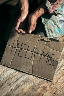 Mãos de mendigo masculinas em busca de dinheiro com sinal me ajudem da bondade humana no chão de madeira no caminho do caminho público ou passagem da rua. pobres sem teto na cidade. problemas com finanças, local de residência.