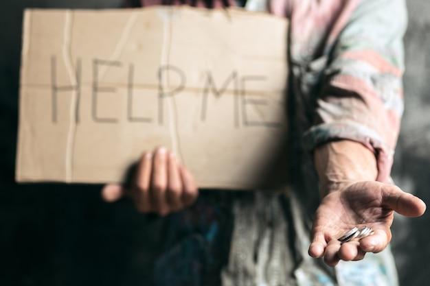 Mãos de mendigo masculinas em busca de dinheiro, moedas da bondade humana no chão de madeira na via pública ou passagem de rua. pobres sem teto na cidade. problemas com finanças, local de residência.