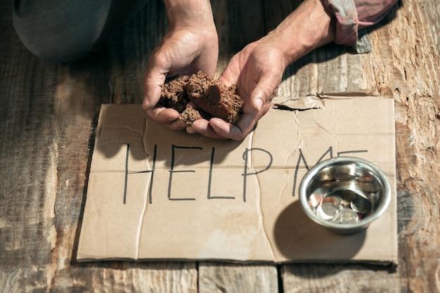Mãos de mendigo masculinos em busca de dinheiro com sinal me ajudem da bondade humana no chão de madeira no caminho do caminho público ou passagem da rua. pobres sem teto na cidade. problemas com finanças, local de residência.