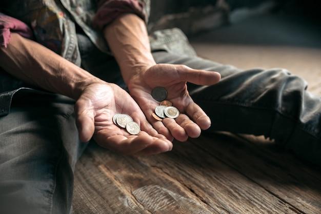 Mãos de mendigo procurando moedas de dinheiro da bondade humana no chão de madeira