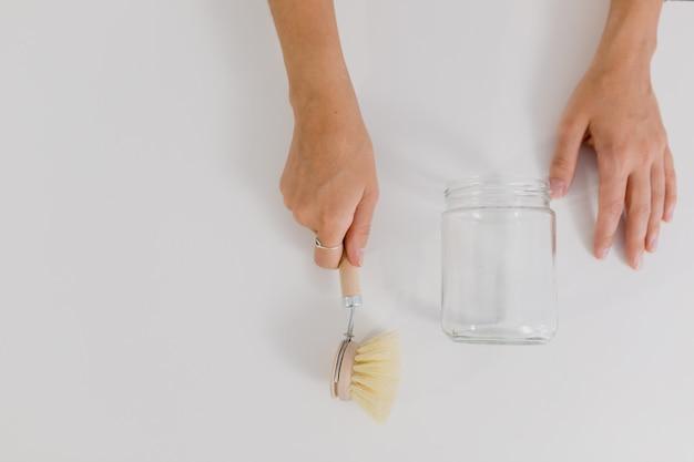 Mãos de menina com recipiente de vidro e escova de madeira
