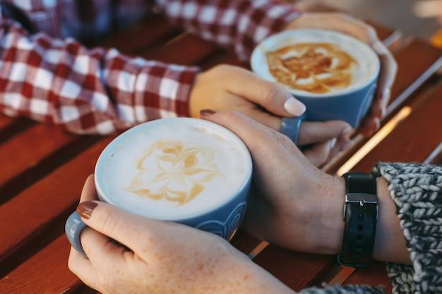 Mãos de menina com sardas segurando xícaras de café