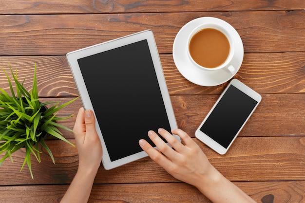 Mãos de menina com tablet digital e xícara de café em uma mesa de madeira