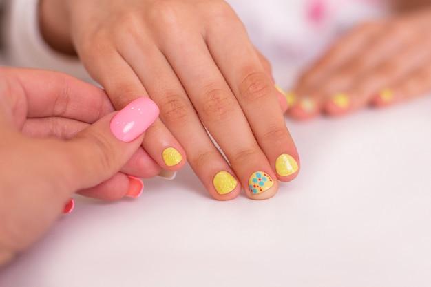 Mãos de menina com unhas manicure amarelo, desenho de flores
