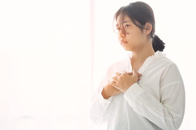 Mãos de menina orando a deus. jovem, ore pela bênção de deus para desejar uma vida melhor. implorando por perdão e acreditando na bondade. oração da crise da vida cristã a deus