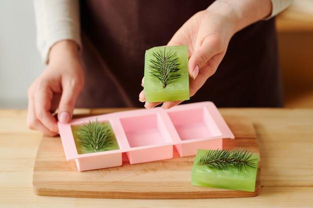 Mãos de menina segurando sabonete artesanal verde fresco com conífera no topo depois de retirá-lo do molde de silicone