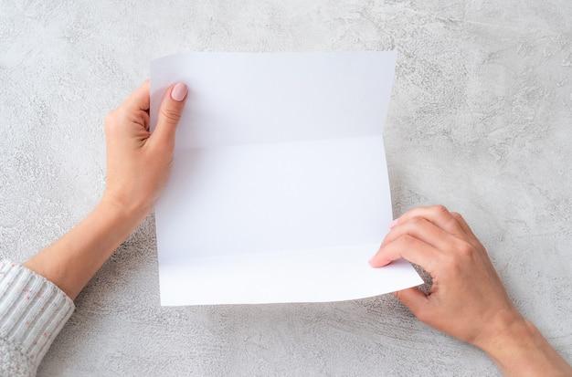 Mãos de menina segurando uma folha de papel branca