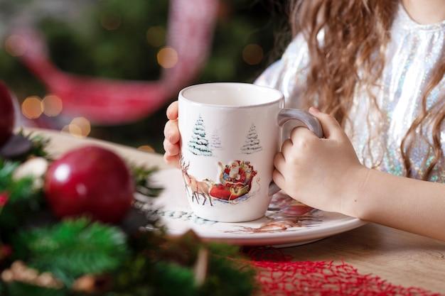 Mãos de menina segurando uma xícara de chá em pé sobre a mesa