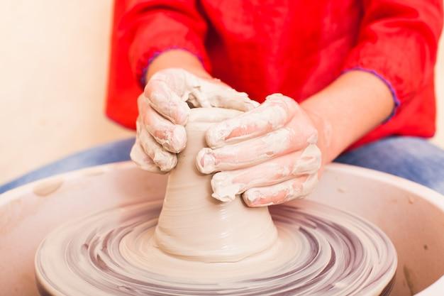 Mãos de menina tentando fazer cerâmica de argila branca em uma roda de oleiro