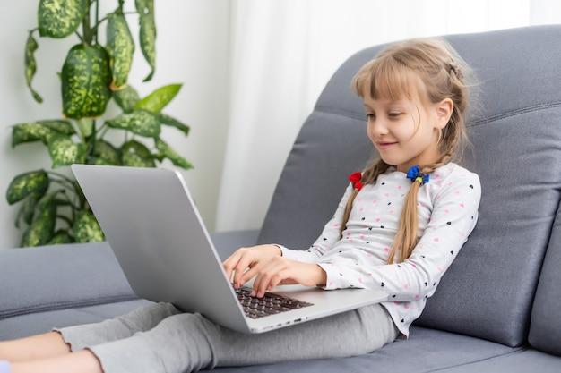 Mãos de menina usando o laptop. compras online na infância.