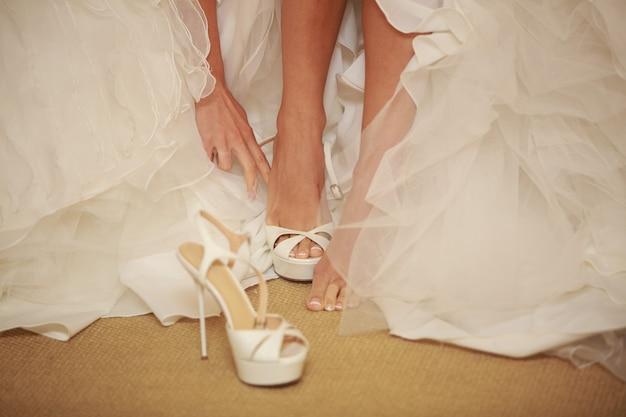 Mãos de meninas calçam sapatos de salto alto, mãos de mulheres em fechos de vestido longo branco e sandálias de roupa