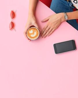 Mãos de meninas segurando uma xícara de café mesa de escritório em casa
