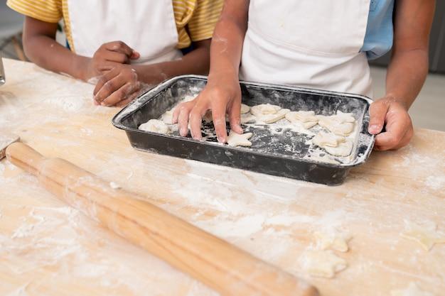 Mãos de menino cortando biscoitos da massa enrolada enquanto cozinha massa para a ceia de natal