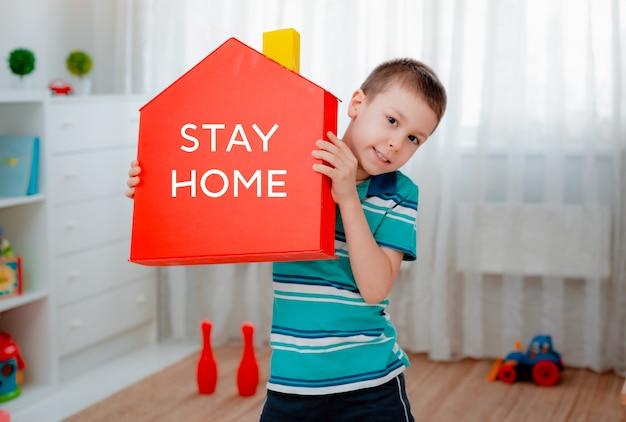 Mãos de menino crianças segurando o modelo de casa vermelha com palavras