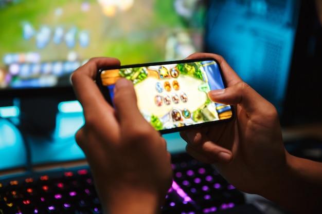 Mãos de menino jogador jogando videogame no smartphone e computador em um quarto escuro, usando fones de ouvido e usando o teclado colorido com luz de fundo
